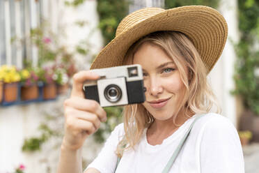 Portrait of smiling young woman with camera - AFVF05438