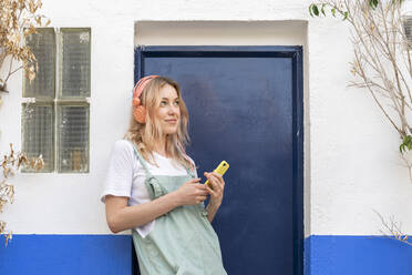 Portrait of young blond woman  leaning at facade listening music with headphones and smartphone - AFVF05444