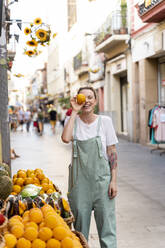 Portrait of laughing young woman on shopping street covering eye with an orange - AFVF05450