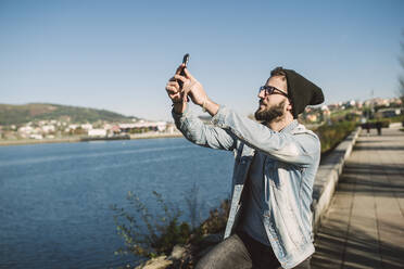 Young man taking smartphone selfies by the sea - RAEF02338