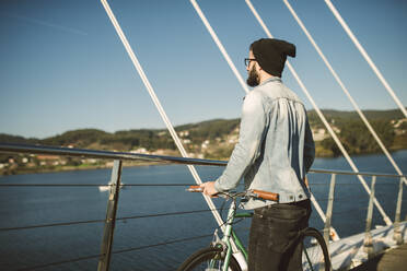 Young man commuting in the city with fis fixie bike, looking at the sea - RAEF02341