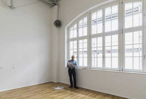 Man checking specifications of refurbished kuxury loft - GWF06442