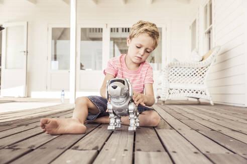 Boy playing with robot dog on veranda - SDAHF00237