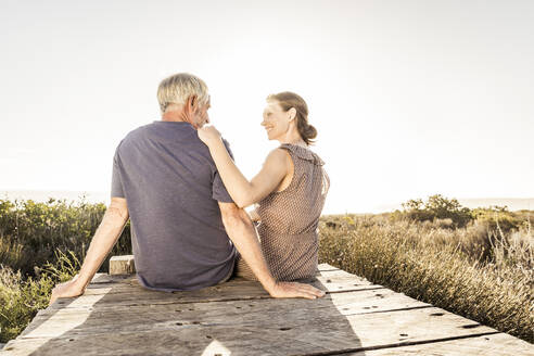 Rear view of couple sitting on boardwalk at sunset - SDAHF00267
