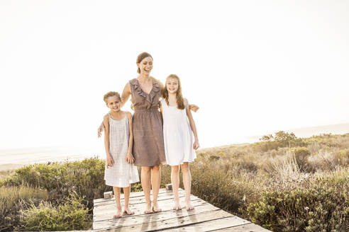 Happy mother embracing her two daughters on a boardwalk at sunset - SDAHF00273
