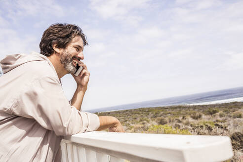 Man wearing bathrobe and phoning with smartphone on a terrace - SDAHF00288