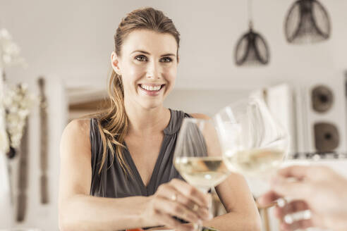 Portrait of smiling young woman having dinner with boyfriend clinking wine glasses - SDAHF00300