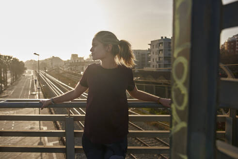 Sporty young woman standing on a bridge at sunset - PACF00194