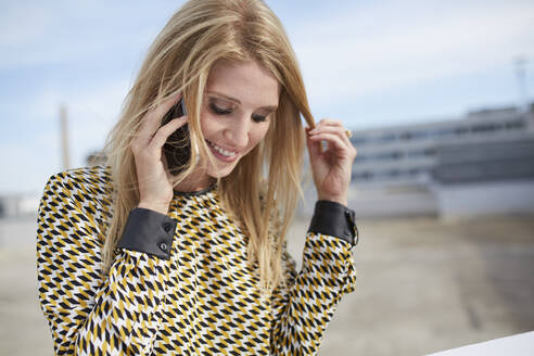 Portrait of smiling blond young woman on the phone - PNEF02329