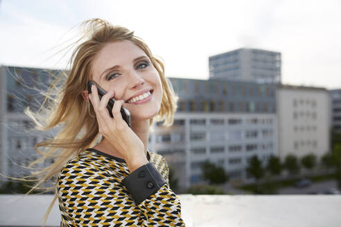 Portrait of happy blond young woman with windblown hair on the phone - PNEF02332