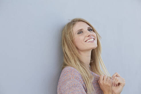 Portrait of smiling blond young woman wearing a knit jumper leaning against a wall - PNEF02347
