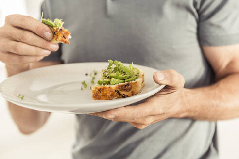 Close-up of man holding a plate with a healthy avocado bread - SDAHF00312
