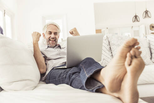 Mature man with laptop cheering on couch at home - SDAHF00330