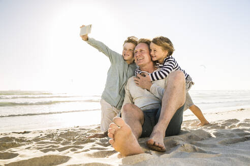 Boy with brother and father taking a selfie on the beach - SDAHF00349