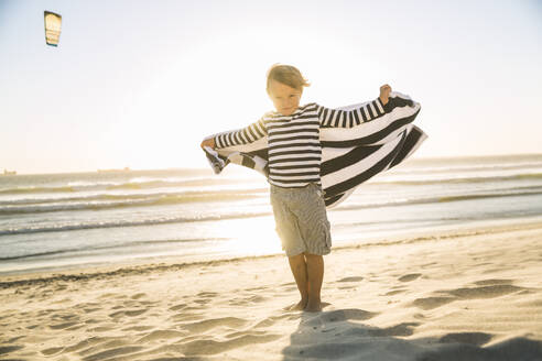 Boy with a towel standing on the beach at sunset - SDAHF00361