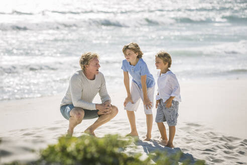 Father having fun with his sons on the beach, playing together - SDAHF00373