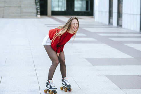 Blond woman rollerskating on a square - KIJF02891