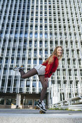 Blond woman balancing with roller skates - KIJF02894