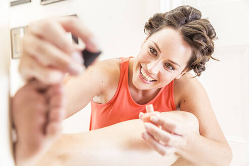 Portrait of happy woman with curlers  painting toenails - SDAHF00442
