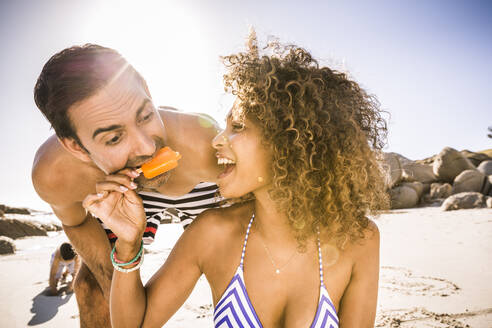 Woman sharing popsicle with man on the beach - SDAHF00469