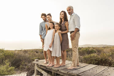 Large family enjoying the sunset standing on a boardwalk - SDAHF00481
