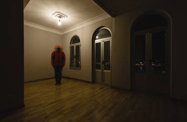 Trembling person standing in empty room at night - RAEF02353