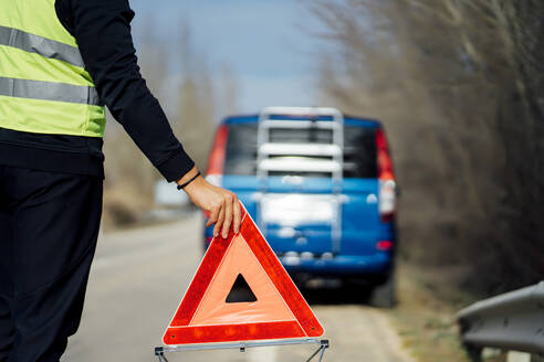 Man putting warning triangle on country road by van breakdown - CJMF00256