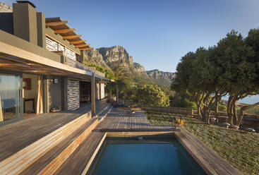 Mountains in background of luxury home showcase exterior house with swimming pool - HOXF04903