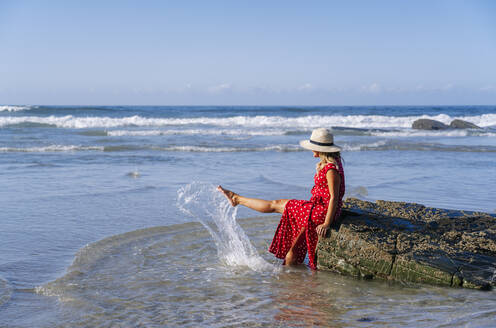 Blond woman wearing red dress and hat sittig on rock at the beach, Playa de Las Catedrales, Spain - DGOF00385