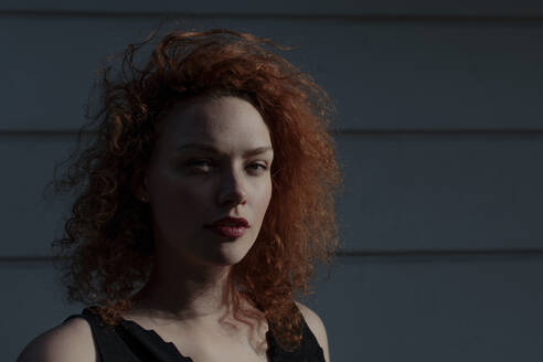 Portrait of red-haired woman looking at camera, wall in the background - OGF00121