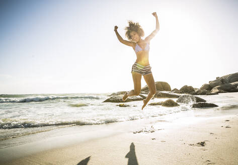 Happy young woman jumping on the beach - SDAHF00507
