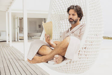 Relaxed man in bathrobe reading a book in hanging chair - SDAHF00531