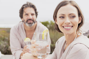 Happy relaxed couple with drinks on terrace - SDAHF00537