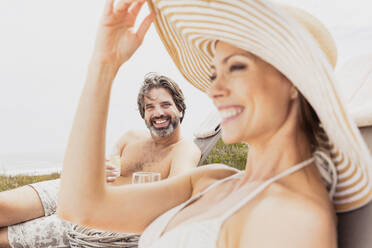 Happy couple relaxing on sun loungers - SDAHF00540