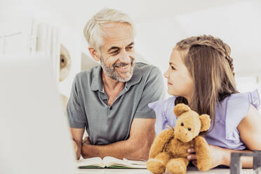 Grey-haired man with laptop and notebook smiling at girl with teddy bear at home - SDAHF00549