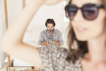 Bearded man sitting on bed with old-fashioned camera with woman in foreground - SDAHF00561