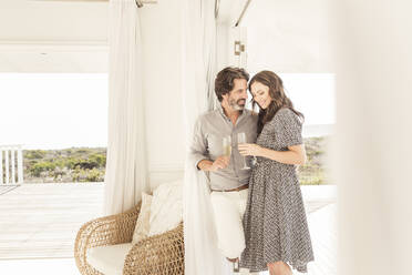 Happy couple drinking champagne in vacation home - SDAHF00567