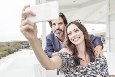 Smiling couple taking a selfie at a vacation home - SDAHF00573