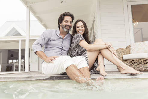 Happy couple relaxing at the poolside of a vacation home - SDAHF00576
