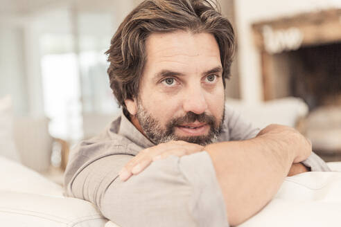 Portrait of bearded man sitting on couch - SDAHF00582