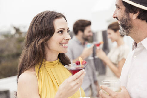 Couple and friends socializing on a cocktail party - SDAHF00585