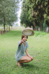 Young woman on a meadow throwing a hat - GIOF07997