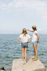 Two female friends standing at the lakeside, Lake Garda, Italy - GIOF08000