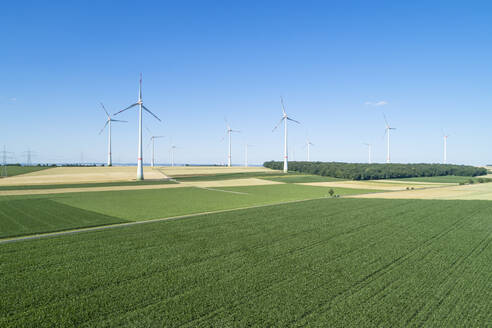 Germany, Bavaria, Drone view of green countryside fields in summer with wind farm in background - RUEF02614