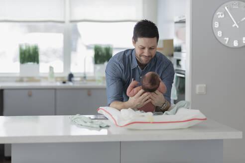 Man changing babys diaper - JOHF08913