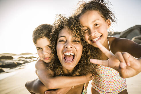 Portrait of a happy mother with her two kids having fun on the beach - SDAHF00605