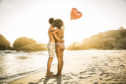Couple with heart-shaped balloon embracing on the beach at sunset - SDAHF00614