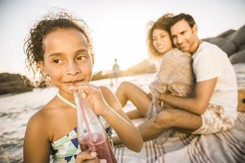 Girl with her family having a soft drink at sunset at the beach - SDAHF00617
