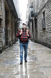 Senior man walking in the city, Barcelona, Spain - JCZF00013