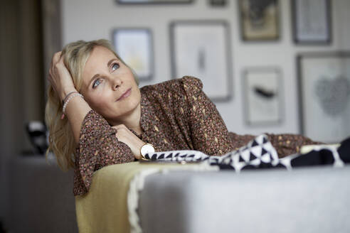 Blond woman relaxing at home sitting on couch - RBF07048